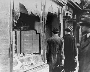 1270px-Germans_walk_by_a_Jewish_business_destroyed_on_Kristallnacht.jpg