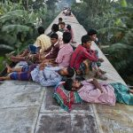 bangladeshis-sleep-on-the-roof-of-a-moving-train-as-they-rush-home-to-their-respective-villages-to-be-with-their-families-in-dhak